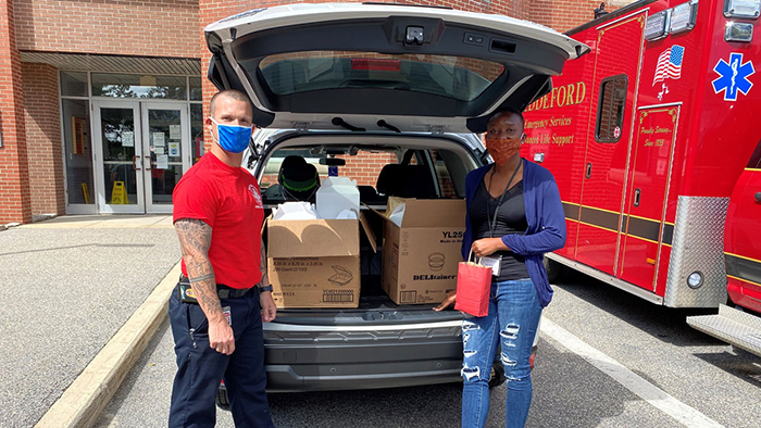 Two volunteers stand by an open car trunk full of donations